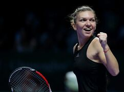 Romania's Simona Halep celebrates after defeating Poland's Agnieszka Radwanska in their semifinal match at the WTA tennis finals in Singapore, Saturday, Oct. 25, 2014. (AP Photo/Mark Baker)