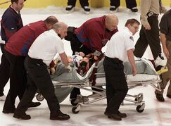 FILE - In this March 8, 2004, file photo, Colorado Avalanche NHL hockey player Steve Moore is taken off the ice by medical staff after he was hit by Vancouver Canucks' Todd Bertuzzi during the third period of NHL action in Vancouver, British Columbia. A settlement has been reached in Moore's lawsuit against Bertuzzi for his career-ending hit during an NHL game 10 years ago. THE CANADIAN PRESS/Chuck Stoody