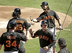 San Francisco Giants' Gregor Blanco, front right, and Angel Pagan, back right, celebrate with Andrew Susac (34) and Brandon Crawford (35) after Blanco and Pagan scored on a triple by Travis Ishikawa during the second inning of a spring training baseball game against the Texas Rangers Friday, March 6, 2015, in Surprise, Ariz. (AP Photo/Charlie Riedel)
