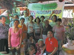 Community correspondent Reyn Cruz (seated, in red shirt) and volunteers Rodan Delizo, Cecilia Cruz, Rizalina Delizo, April Santos and Lourdes Galligues pose with the beneficiary families after delivering Christmas hampers from PGM to the town of San Quintin.