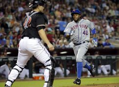 Arizona Diamondbacks catcher Miguel Montero, left, waits for the throw as New York Mets' Eric Young Jr. scores on a hit by teammate Daniel Murphy during the fourth inning of the MLB National League baseball game on Tuesday, April 15, 2014, in Phoenix. (AP Photo/Matt York)