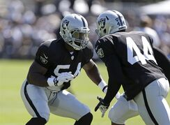Oakland Raiders linebackers Marshall McFadden, left, and Carlos Fields, right, take part in a drill during NFL football training camp Sunday, July 27, 2014, in Napa, Calif. (AP Photo/Eric Risberg)