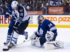 Toronto Maple Leafs goalie James Reimer (34) makes a save as he is screened by Winnipeg Jets forward Andrew Ladd (16) during the first period in Toronto on Saturday.
