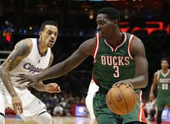 Milwaukee Bucks' Johnny O'Bryant III, right, dribbles against Los Angeles Clippers' Matt Barnes during the first half of an NBA basketball game Saturday, Dec. 20, 2014, in Los Angeles. (AP Photo/Danny Moloshok)