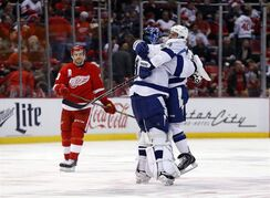 Tampa Bay Lightning goalie Ben Bishop, middle, celebrates with Ryan Callahan as Detroit Red Wings center Pavel Datsyuk (13) skates off the ice after a Tyler Johnson goal in overtime of Game 4 of a first-round NHL Stanley Cup hockey playoff series Thursday, April 23, 2015, in Detroit. Tampa Bay won 3-2 in overtime. (AP Photo/Paul Sancya)