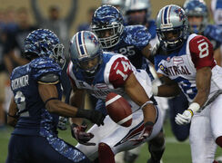 Winnipeg Blue Bombers Matt Bucknor, left, wrestles for the ball along with Montreal Alouettes Brandon London, centre, and Kenny Stafford during first half CFL action at Investors Group Field in Winnipeg Friday night.