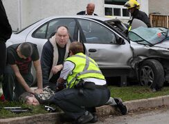 A bystander restrains a person who was alleged to have caused a three car crash and was then seen brandishing a knife, saying he wanted to get out of here because he was drunk.