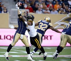 Winnipeg Blue Bombers' quarterback Drew Willy (5) is hit by Hamilton Tiger-Cats' Eric Norwood (40) as he releases the ball during the first half of Saturday's game.