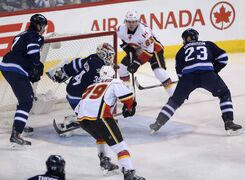 Calgary Flames' Sam Bennett (63) at the side of the net and Michael Ferland (79) right before Ferland opened the scoring on Winnipeg Jets' goaltender Michael Hutchinson (34) in the first minute of NHL hockey action on Saturday.
