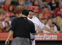 Los Angeles Angels manager Mike Scioscia, right, argues with home plate umpire Eric Cooper after Los Angeles Angels' Mike Trout was called out on strikes during the seventh inning of a baseball game against the Baltimore Orioles on Monday, July 21, 2014, in Anaheim, Calif. (AP Photo/Jae C. Hong)