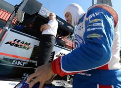 Helio Castroneves, right, prepares for practice for Saturday's Indycar auto race Friday, Aug. 29, 2014, at Auto Club Speedway, in Fontana, Calif., as team owner Roger Penske stands nearby. (AP Photo/Will Lester)