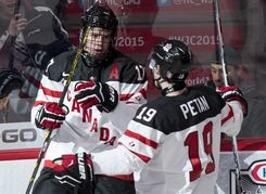 Team Canada's Connor McDavid, left, celebrates his goal against Team Germany with teammate Nic Petan during first period preliminary round hockey action at the IIHF World Junior Championship Saturday, December 27, 2014 in Montreal. THE CANADIAN PRESS/Paul Chiasson