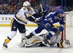 Tampa Bay Lightning's Ryan Callahan, middle, is checked over Nashville Predators goalie Pekka Rinne by defenceman Roman Josi during the second period of an NHL hockey game Thursday, March 26, 2015, in Tampa, Fla. THE CANADIAN PRESS/AP/Mike Carlson