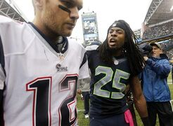 FILE - In this Oct. 14, 2014, file photo, Seattle Seahawks' Richard Sherman (25) talks with New England Patriots quarterback Tom Brady after the Seahawks won 24-23 in an NFL football game in Seattle. Sherman already gave Brady an earful the last time the Seahawks played the Patriots. This Super Bowl could feature some epic yapping from some of the best trash-talkers in the NFL. (AP Photo/Elaine Thompson)