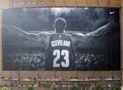 FILE - In this Oct. 30, 2014, file photo, workers finish hanging a mural of Cleveland Cavaliers' LeBron James on a building in Cleveland. James' return to Cleveland was the third-ranked sports story of the year Tuesday, Dec. 23, 2014, in an annual vote conducted by The Associated Press. The NFL's troubles with domestic violence was the top story of the year. (AP Photo/Mark Duncan, File)