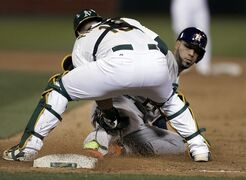 Houston Astros' Marwin Gonzalez, right, is tagged out by Oakland Athletics catcher Josh Phegley at first base during a rundown in the eighth inning of a baseball game Friday, April 24, 2015, in Oakland, Calif. (AP Photo/Ben Margot)