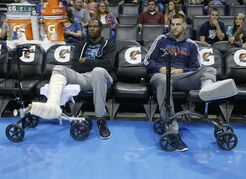 Oklahoma City Thunder forwards Kevin Durant, left, and forward Mitch McGary, right, prop up their injured feet as they watch players warm up for a preseason NBA basketball game between the Thunder and the Utah Jazz in Oklahoma City, Tuesday, Oct. 21, 2014. (AP Photo/Sue Ogrocki)