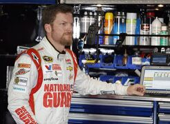 Dale Earnhardt Jr. waits in the garage stall as his car is adjusted during a practice session for Sunday's NASCAR Sprint Cup Series auto race at Pocono Raceway, Friday, Aug. 1, 2014, in Long Pond, Pa. (AP Photo/Matt Slocum)