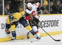 Nashville Predators center Craig Smith (15) battles for the puck with Calgary Flames defenseman Deryk Engelland (29) in the first period of an NHL hockey game Sunday, March 29, 2015, in Nashville, Tenn. (AP Photo/Mark Humphrey)
