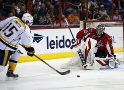 Nashville Predators center Craig Smith (15) shoots but has his shot stopped by Washington Capitals goalie Justin Peters (35) in the second period of an NHL hockey game Saturday, March 28, 2015, in Washington. (AP Photo/Alex Brandon)