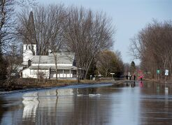 Water from the St. John River covers the highway in Maugerville, N.B. on Thursday, April 17, 2014. Rain, melting snow and ice jams forced waters in parts of Eastern Canada to rise, submerging roads, filling basements and prompting hundreds to be evacuated from their homes. THE CANADIAN PRESS/Andrew Vaughan