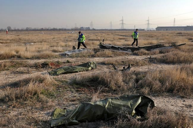 Rescue workers search the scene where a Ukrainian plane crashed as the bodies of victims in body bags lie on the ground, in Shahedshahr, southwest of the capital Tehran, Iran, Wednesday, Jan. 8, 2020. A Ukrainian airplane with more than 170 people crashed on Wednesday shortly after takeoff from Tehran's main airport, killing all onboard. (AP Photo/Ebrahim Noroozi)