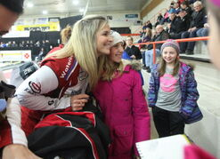 Olympic gold medalist curler Jennifer Jones has her picture taken with young curler, Rayna Krahn, 12, as her friend, Hope Friesen (right) looks on.