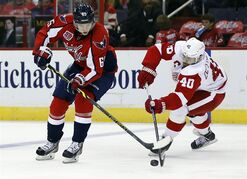 Washington Capitals left wing Andre Burakovsky (65), from Austria, goes for the puck with Detroit Red Wings left wing Henrik Zetterberg (40), from Sweden, in the second period of an NHL hockey game, Wednesday, Oct. 29, 2014, in Washington. (AP Photo/Alex Brandon)