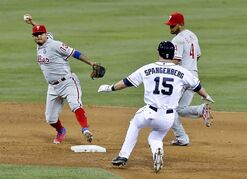 Philadelphia Phillies' Andres Blanco (4) looks on as teammate Freddy Galvis makes the out at second on San Diego Padres' Cory Spangenberg while turning the double play during the sixth inning in a baseball game Thursday, Sept. 18, 2014, in San Diego. San Diego won the game 7-3. (AP Photo/Don Boomer)