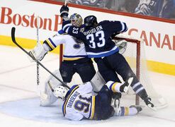 Winnipeg Jets power forward Dustin Byfuglien and the St. Louis Blues' Vladimir Tarasenko crash into Blues goalie Jake Allen during third period NHL action at the MTS Centre Sunday.