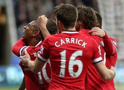 Manchester United's Ashley Young, left, celebrates his goal with his teammates during their English Premier League soccer match between Newcastle United and Manchester United at St James' Park, Newcastle, England, Wednesday, March, 4, 2015. (AP Photo/Scott Heppell)
