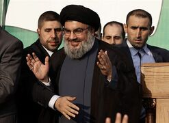 In this Sept. 17, 2012 photo, Hezbollah leader Sheik Hassan Nasrallah, center, waves to his supporters, in the southern suburb of Beirut, Lebanon. THE CANADIAN PRESS/AP, Hussein Malla