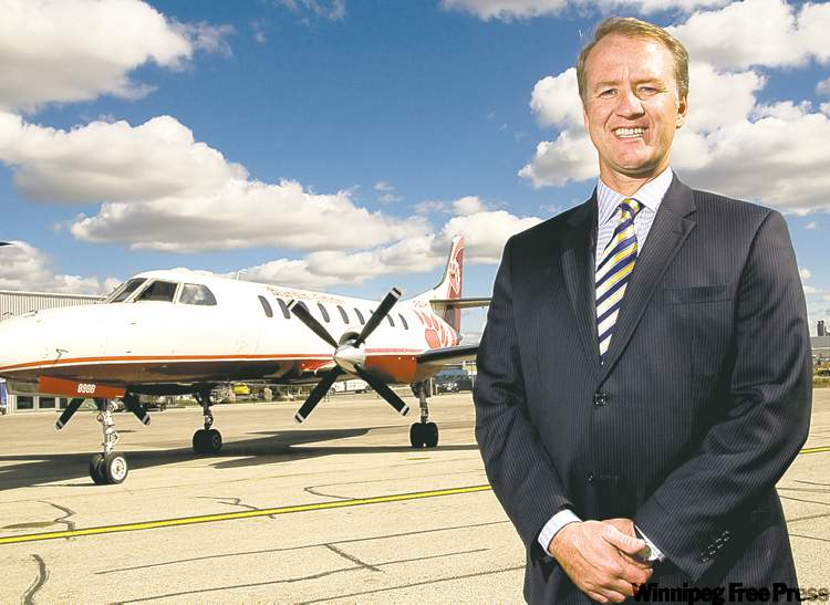 Exchange Income Corporation's Michael Rodyniuk with a Bearskin Airlines plane at Calm Air Wednesday afternoon.