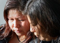 Tina Duck (left) is comforted by her sister, Samantha Green. Duck is the mother of Tina Fontaine, who was killed in August.