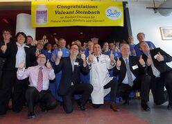 MLA Kevin Chief (wearing lab coat) leads the crew at Valeant Canada's Steinbach facility in a celebratory team photo.