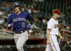 Colorado Rockies' Troy Tulowitzki (2) scores on a ground out by teammate Nolan Arenado during the sixth inning of a baseball game as Arizona Diamondbacks pitcher Chase Anderson, right, walks to the mound, Monday, April 27, 2015, in Phoenix. (AP Photo/Matt York)