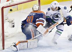 Vancouver Canucks' Yannick Weber (6) scores a goal against Edmonton Oilers goalie Ben Scrivens (30) during third period NHL hockey action in Edmonton on Wednesday November 19, 2014. THE CANADIAN PRESS/Jason Franson