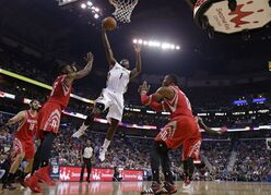 New Orleans Pelicans forward Tyreke Evans (1) goes to the basket between Houston Rockets forward Terrence Jones (6) and center Dwight Howard (12) in the first half of an NBA basketball game in New Orleans, Wednesday, April 16, 2014. (AP Photo/Gerald Herbert)