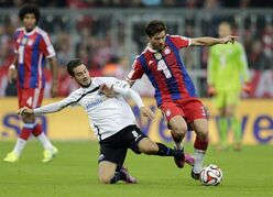 Paderborn's Mario Vrancic, left, and Bayern's Xabi Alonso of Spain challenge for the ball during the German first division Bundesliga soccer match between FC Bayern and SC Paderborn 07 in the Allianz Arena in Munich, Germany, on Tuesday, Sept. 23, 2014. (AP Photo/Matthias Schrader)
