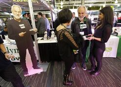 FILE - In this Feb. 19, 2015 file photo, comedian and marijuana icon Tommy Chong, second from right, talks to visitors as he stands near a life-sized cardboard cut-out of himself, while promoting his line of marijuana products, including his