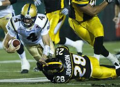 Winnipeg Blue Bombers quarterback Buck Pierce, left, gets tackled by Hamilton Tiger-Cats linebacker Jamall Johnson during first-half CFL football action in Hamilton Friday.