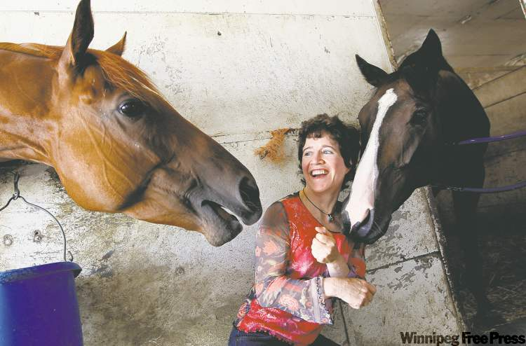 Vicky Baze, one of the top female jockeys in North America, shares some horsey humour with  Action Sketch (left)  and Vinegar Bend at  Assiniboia Downs.