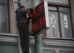 A worker repairs an electronic display board with figures indicating the US dollar to Russian ruble exchange rate outside a currency exchange office in St.Petersburg, Russia, Sunday, Dec. 28, 2014. The ruble has been the worst performing currency this year along with the Ukrainian hryvnia, having lost nearly half of its value against the dollar. (AP Photo/Dmitry Lovetsky)