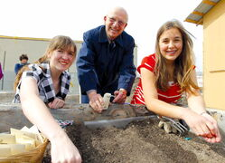Ron O'Donovan, who started Grow a Row with wife Eunice, plants seeds behind Winnipeg Harvest with J.H. Bruns Collegiate students Jamie Campbell and Julia Stoyko on Monday. The girls and their classmates were inspired to help when O'Donovan spoke at their school.