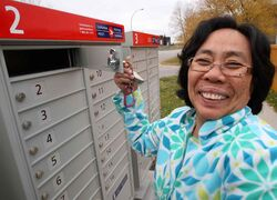Leonora Lipato checks mail in her pajamas in her new Canada Post community mailbox at Jefferson Avenue and Adsum Street Monday morning.