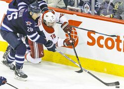 Jets' Blake Wheeler (26) and Coyotes' Shane Doan contend for the puck in second-period play on Thursday night.