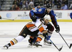 Anaheim Ducks defenseman Clayton Stoner, bottom, and Colorado Avalanche center Tomas Vincour, top, fight for the puck in the first period of an NHL preseason hockey game Monday, Sept. 22, 2014 in Denver. (AP Photo/Chris Schneider)