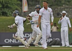 Sri Lankan batsmen Kaushal Silva, left, and Kumar Sangakkara, centre, run between the wickets as South African bowler Dale Steyn watches during the fourth day of the second test cricket match between South Africa and Sri Lanka in Colombo, Sri Lanka, Sunday, July 27, 2014. (AP Photo/Sanka Gayashan)