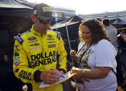 Driver Matt Kenseth signs an autograph for a fan during practice for a NASCAR Sprint Cup Series auto race at Bristol Motor Speedway on Saturday, April 18, 2015, in Bristol, Tenn. (AP Photo/Wade Payne)