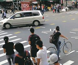 Pedestrians, cyclists and motorists share the street at an intersection in New York City.